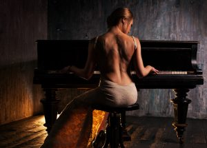 Young elegant woman in evening dress with naked back playing piano in retro style interior. Dark colors and backside view.